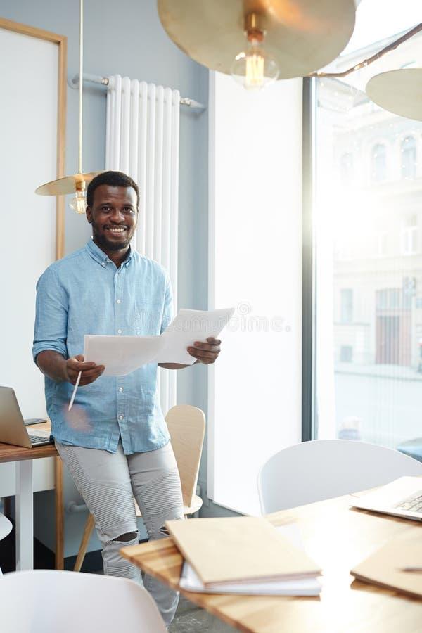 Vrolijke Afrikaans-Amerikaanse mens met documenten in bureau stock afbeelding
