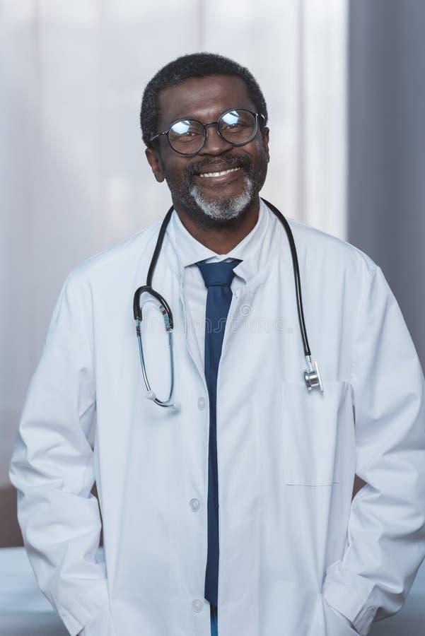 vrolijke Afrikaanse Amerikaanse arts in witte laag met stethoscoop het kijken stock fotografie