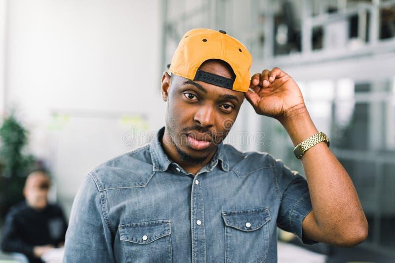 Vrolijke Afrikaanse Amerikaanse hipsterkerel die zich in zolderbureau tijdens vrije tijd bevinden, gelukkige donkere gevilde mens royalty-vrije stock foto