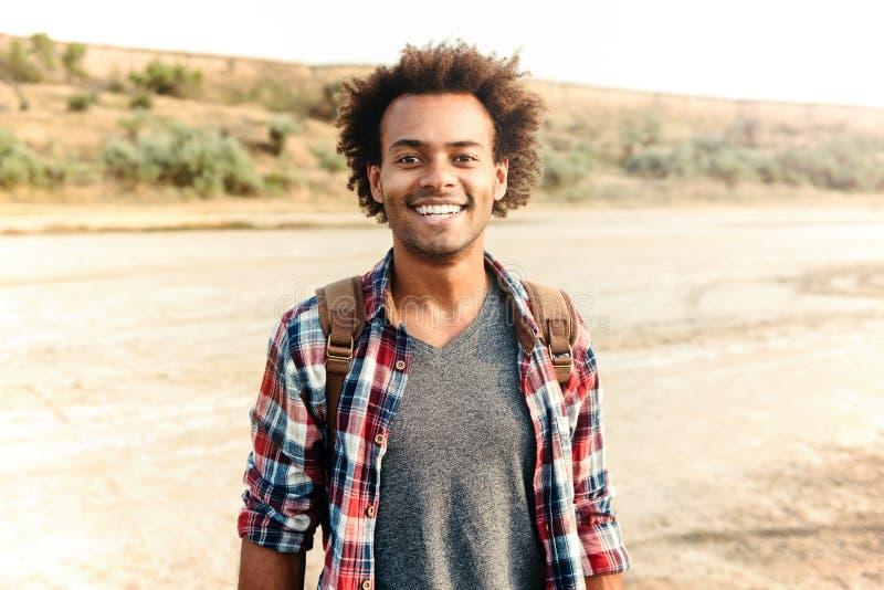 Vrolijke Afrikaanse Amerikaanse jonge mens in plaidoverhemd met rugzak royalty-vrije stock afbeelding