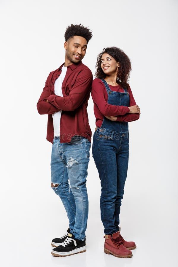 Vrolijke Afrikaanse Amerikaanse man en vrouw met gekruiste handen die zich rijtjes over geïsoleerde witte achtergrond bevinden royalty-vrije stock fotografie