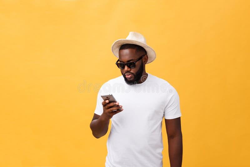 Vrolijke Afrikaanse Amerikaanse mens in wit overhemd die mobiele telefoontoepassing gebruiken gelukkig donker gevild hipster kere stock foto's
