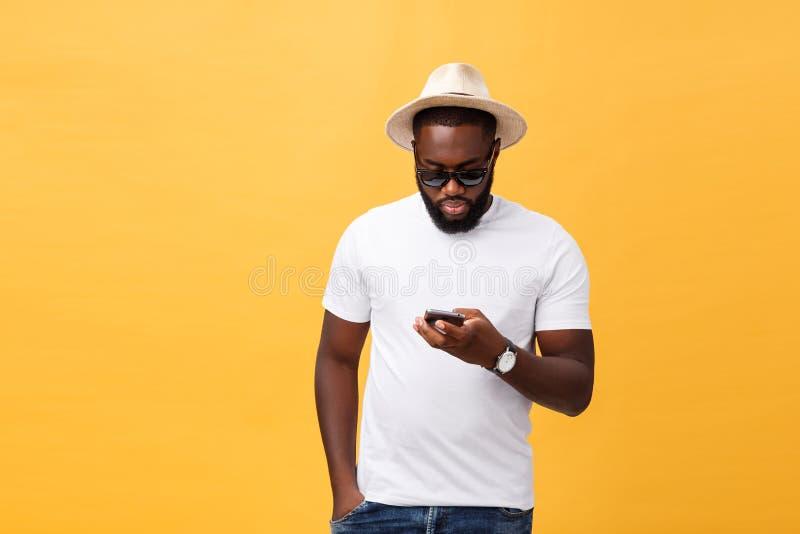 Vrolijke Afrikaanse Amerikaanse mens in wit overhemd die mobiele telefoontoepassing gebruiken gelukkig donker gevild hipster kere stock afbeeldingen