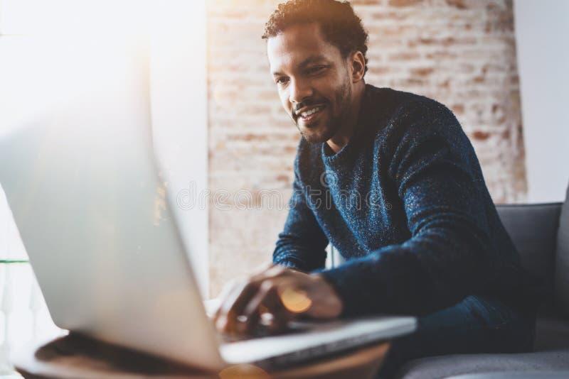 Vrolijke Afrikaanse mens gebruikend computer en glimlachend terwijl het zitten op de bank Concept jonge bedrijfsmensen die werken stock afbeelding