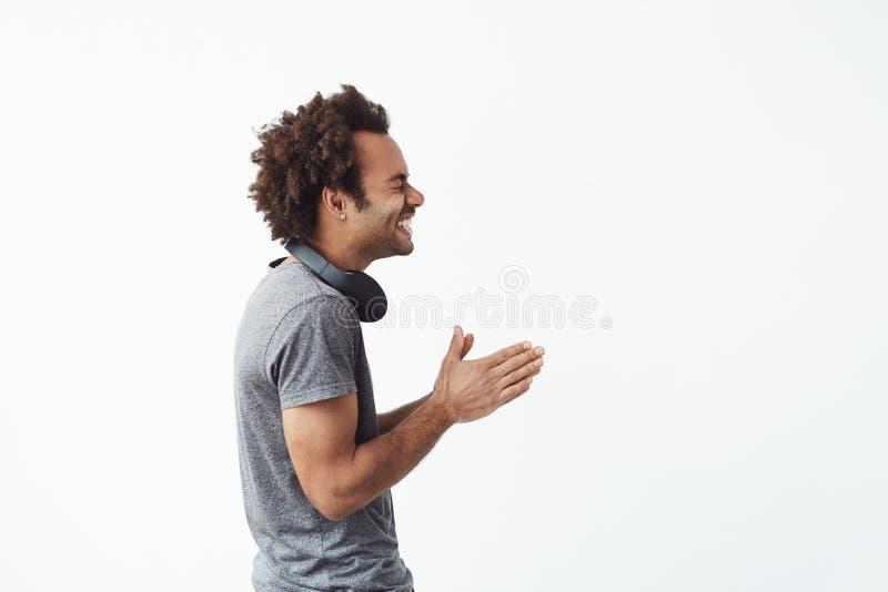 Vrolijke Afrikaanse mens met hoofdtelefoons lachen die zich in profiel over witte achtergrond bevinden royalty-vrije stock afbeelding