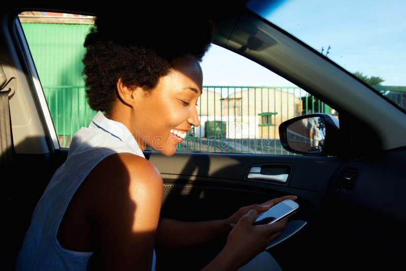 Vrolijke Afrikaanse vrouw die mobiele telefoon in een auto met behulp van stock foto's