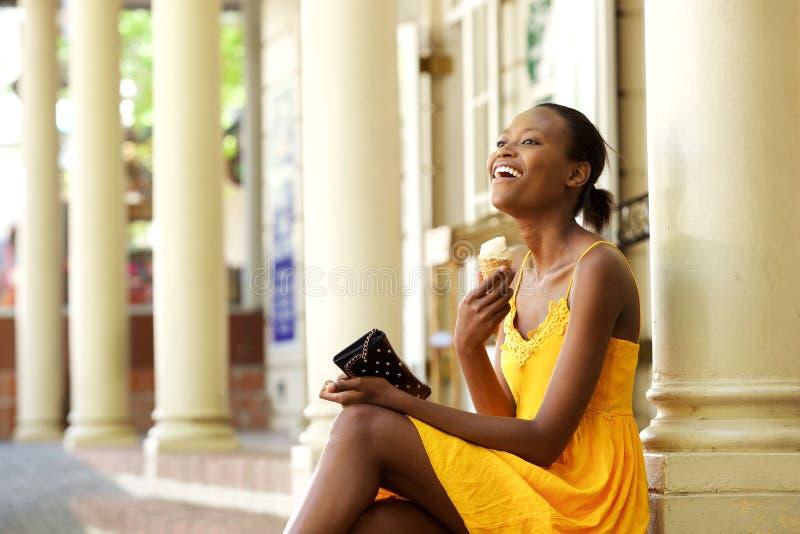 Vrolijke Afrikaanse vrouwenzitting in openlucht met roomijs royalty-vrije stock fotografie