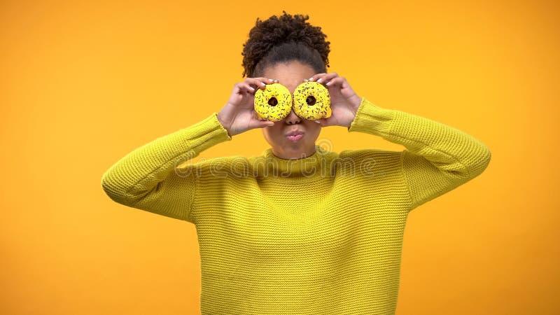 Vrolijke Afro-Amerikaanse meisjes sluitende ogen met donuts, die pret, achtergrond hebben stock afbeelding