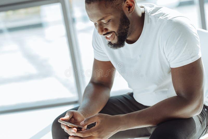 Vrolijke afro Amerikaanse mens die zijn slimme telefoon met behulp van royalty-vrije stock fotografie