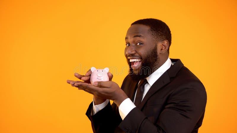 Vrolijke Afro-Amerikaanse mens in en kostuum die piggybank, vertrouwende bank glimlachen houden royalty-vrije stock foto's