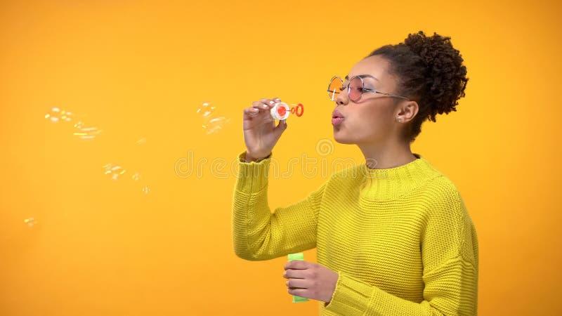 Vrolijke Afro-Amerikaanse vrouwelijke blazende zeepbels, die pret, kinderjarenspel hebben royalty-vrije stock foto