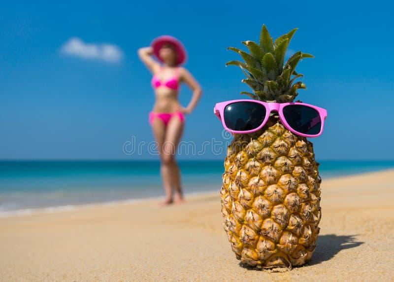 Vrolijke ananasglazen en een vrouw in een bikini die op het strand op overzees backgrounde strand op overzeese achtergrond zonneba stock afbeeldingen