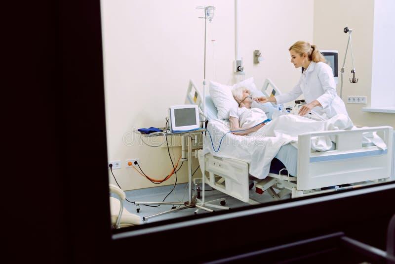 Vrolijke arts die hogere patiënt met zuurstofmasker bezoeken stock fotografie