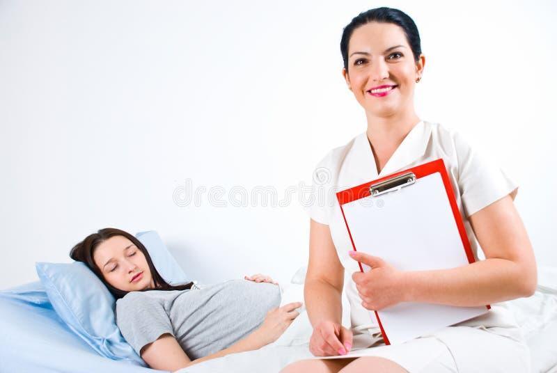 Vrolijke arts met zwangere patiënt stock fotografie