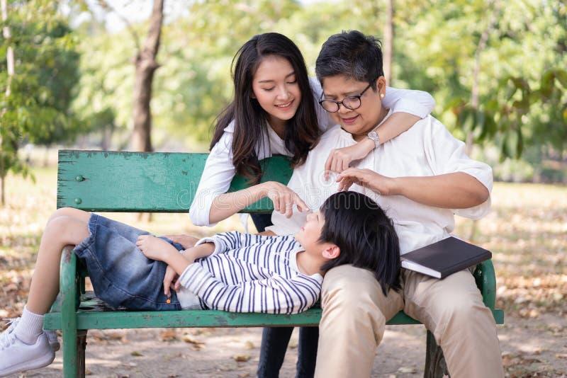 Vrolijke Aziatische familie en ontspanning op de bank samen in het openbare park Het begrip 'levensstijl' in de gezinsvakantie stock afbeelding