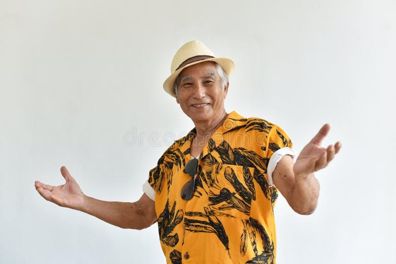 Vrolijke Aziatische hogere oude mens, Zekere en glimlachende bejaarde mensen met welkom gebaar in het kleurrijke overhemd van Haw royalty-vrije stock afbeelding