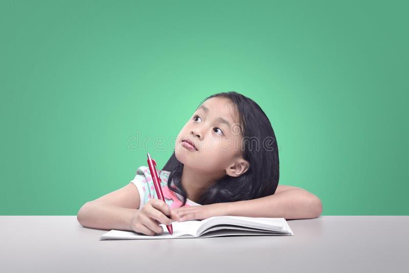 Vrolijke Aziatische kinderen die met pen alvorens op te schrijven denken royalty-vrije stock foto