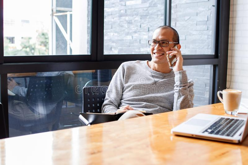 Vrolijke Aziatische mannelijke kleine bedrijfseigenaar die op telefoon met klant spreken terwijl het zitten in bureau De ruimte v stock afbeelding