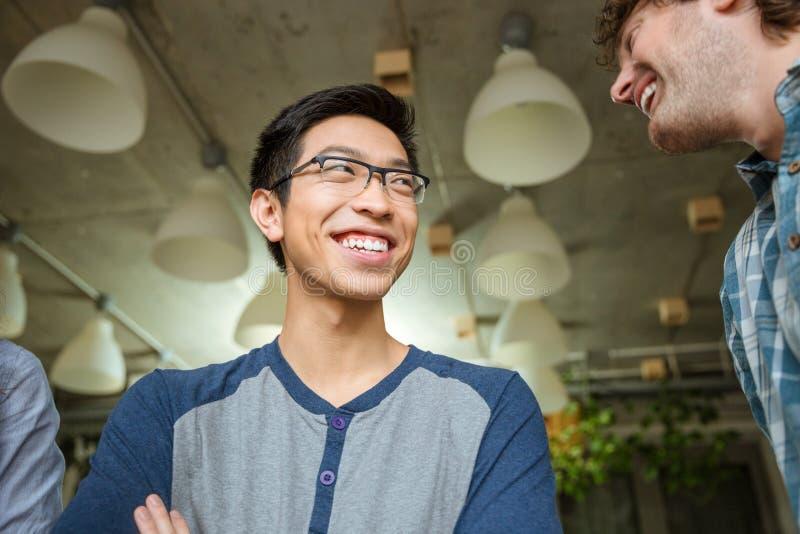 Vrolijke Aziatische mens die met zijn vrienden spreken royalty-vrije stock fotografie
