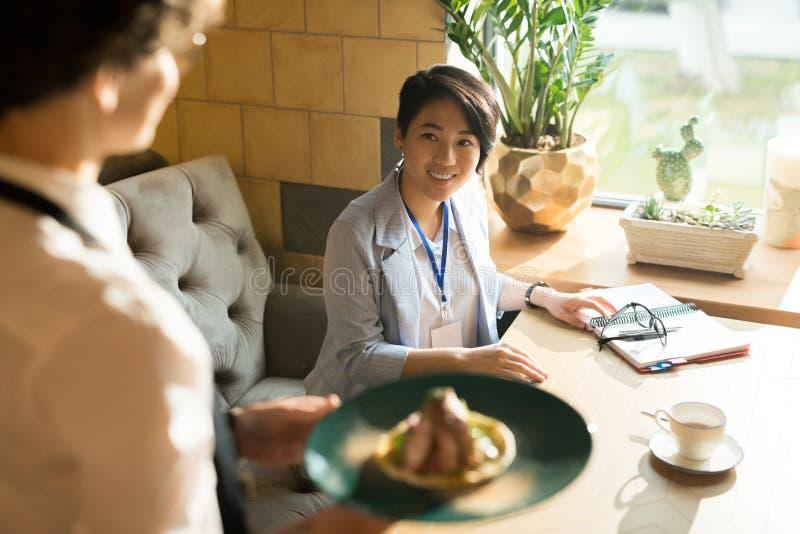 Vrolijke Aziatische vrouw die bij serveerster met haar schotel glimlachen royalty-vrije stock fotografie