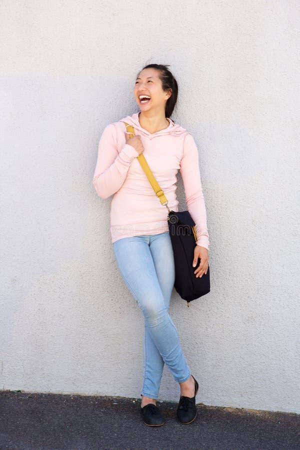 Vrolijke Aziatische vrouw die en zich met zak bevinden lachen stock foto