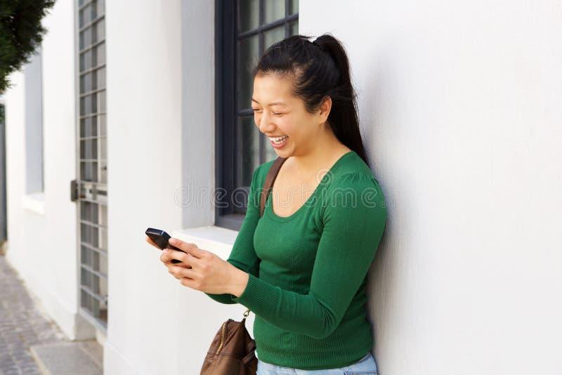 Vrolijke Aziatische vrouw die zich buiten het gebruiken van mobiele telefoon bevinden royalty-vrije stock afbeeldingen