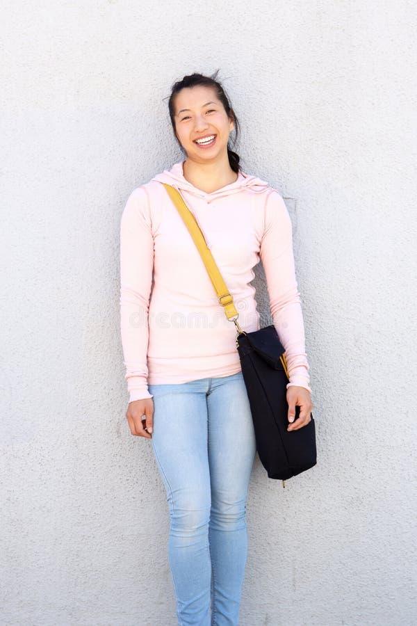 Vrolijke Aziatische vrouw die zich buiten tegen muur met zak bevinden royalty-vrije stock afbeelding
