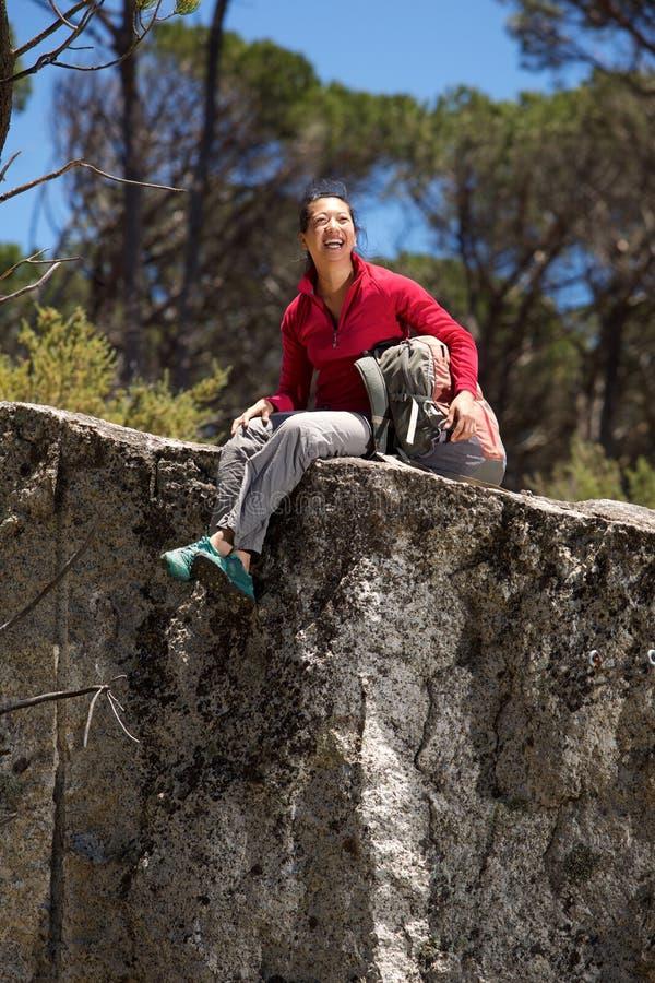 Vrolijke Aziatische vrouwelijke wandelaarzitting bij de rand van berg royalty-vrije stock foto