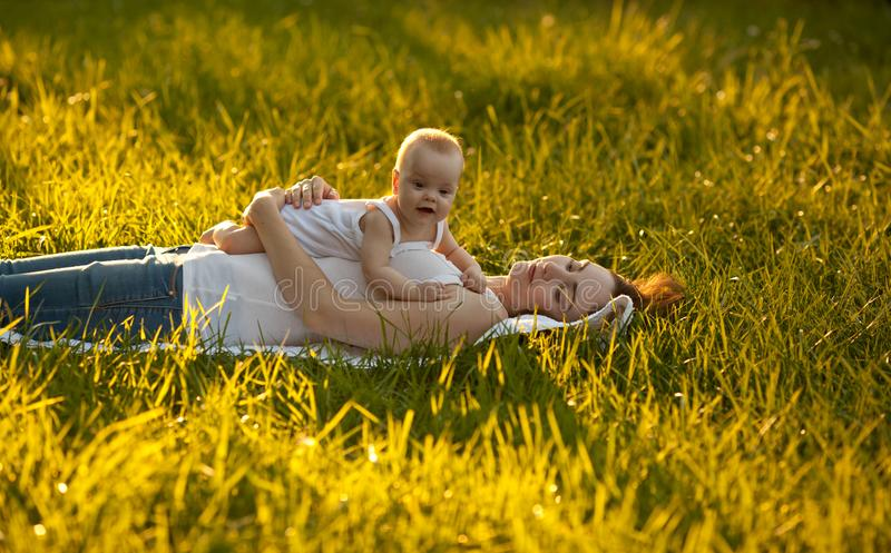 Vrolijke baby die bij haar moeder en het glimlachen liggen royalty-vrije stock fotografie