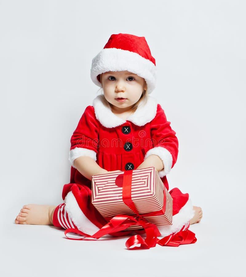 Vrolijke baby in Kerstmanhoed het openen de doos van de Kerstmisgift royalty-vrije stock foto