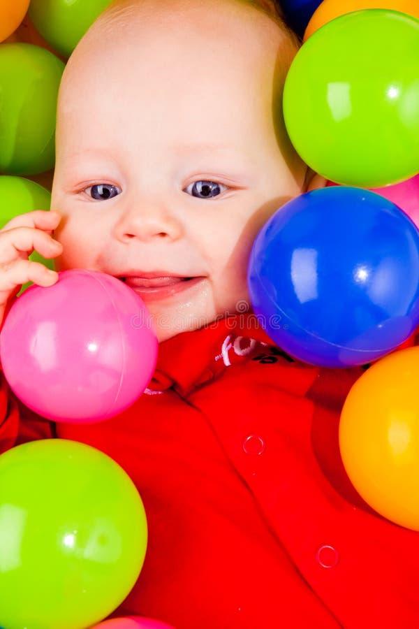 Vrolijke baby met ballen stock foto
