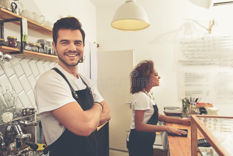 Vrolijke barista die bij teller in koffie werken stock fotografie