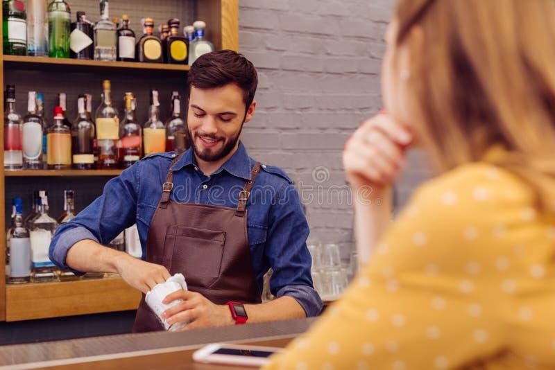 Vrolijke barman die terwijl het schoonmaken van de glazen op het werk glimlachen stock afbeelding