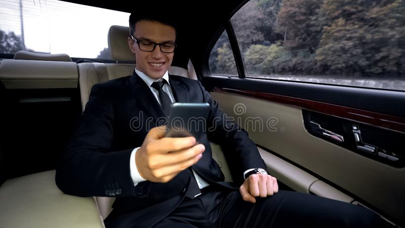 Vrolijke bedrijfsmens die bij telefoon en glimlachen babbelen, die met meisje texting royalty-vrije stock foto's
