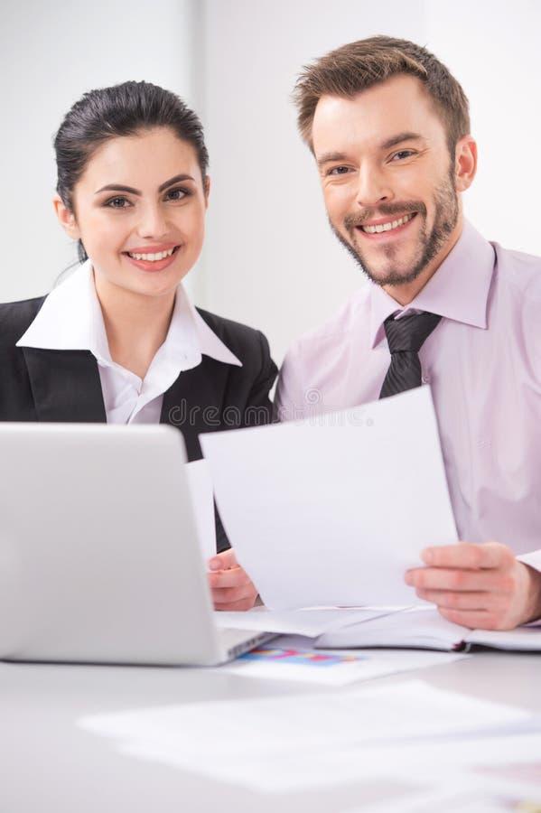Vrolijke bedrijfsmensen die bij lijst met laptop zitten royalty-vrije stock afbeelding