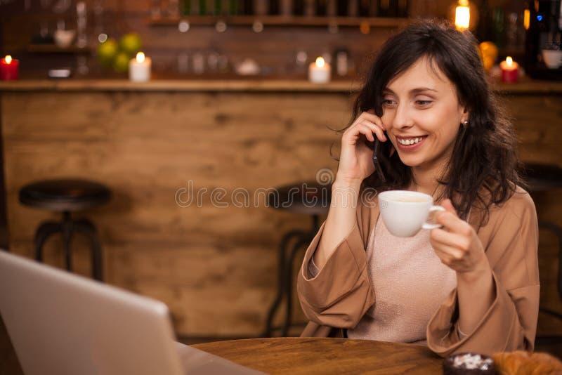 Vrolijke bedrijfsvrouw smilng en bekijkend haar laptop in een koffiewinkel stock fotografie