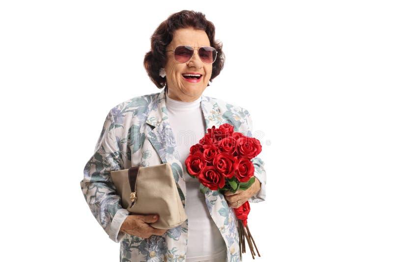 Vrolijke bejaarde dame met een beurs en een bos van rode rozen die bij de camera glimlachen stock foto