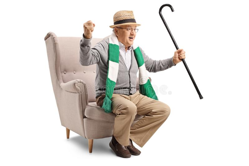 Vrolijke bejaarde sportenventilator met een riet en een sjaalzitting in een leunstoel royalty-vrije stock fotografie