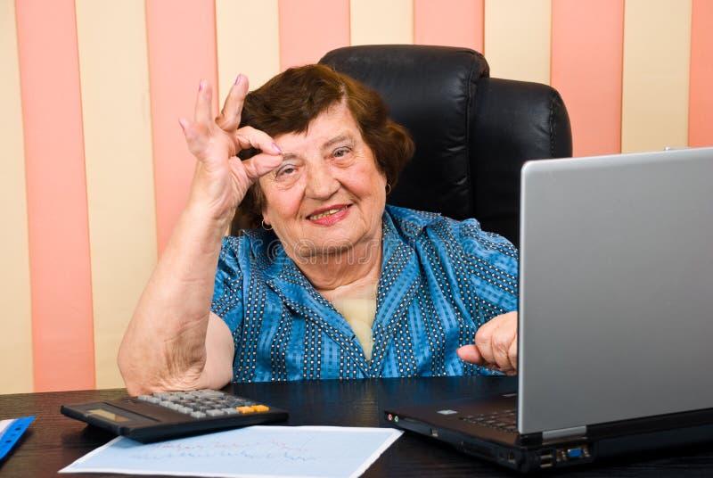 Vrolijke bejaarde stafmedewerker die o.k. tekenhand toont stock foto's
