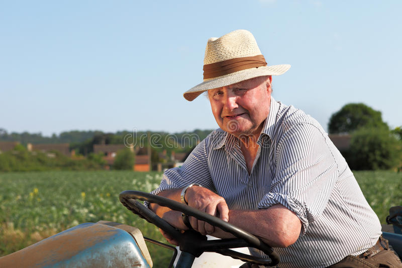 Vrolijke, bejaarde tuinman op zijn tractor royalty-vrije stock fotografie