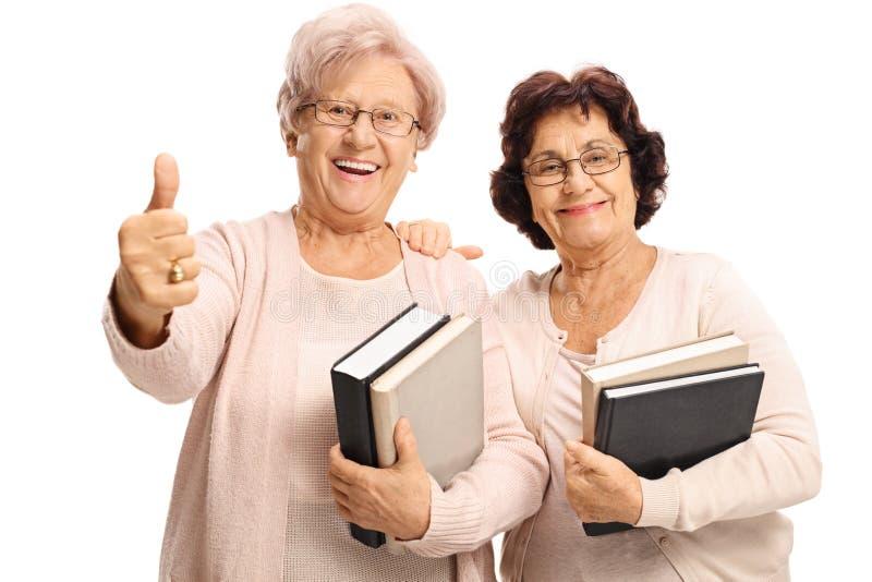 Vrolijke bejaarden die met boeken een duim op gebaar maken royalty-vrije stock foto