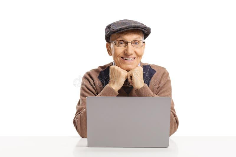 Vrolijke bejaardezitting met een laptop computer voor hem royalty-vrije stock fotografie