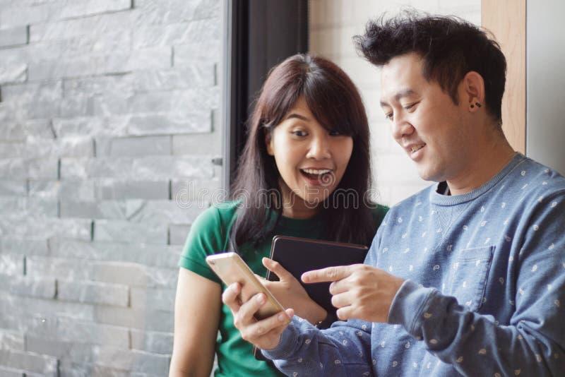 Vrolijke beste vrienden die grappige foto's in sociale netwerken die via smartphone bekijken zich verenigen Selectieve nadruk De  royalty-vrije stock foto
