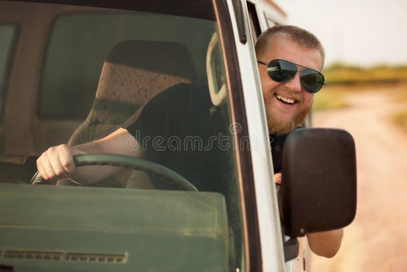 Vrolijke bestuurder achter het wiel van zijn auto royalty-vrije stock fotografie