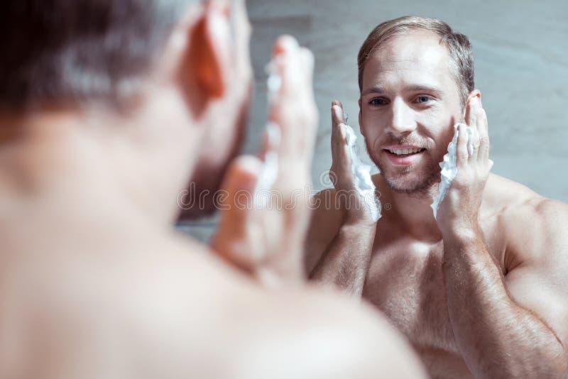 Vrolijke blauw-eyed mens die terwijl het onderzoeken en het scheren het gezicht weerspiegelen glimlachen royalty-vrije stock fotografie