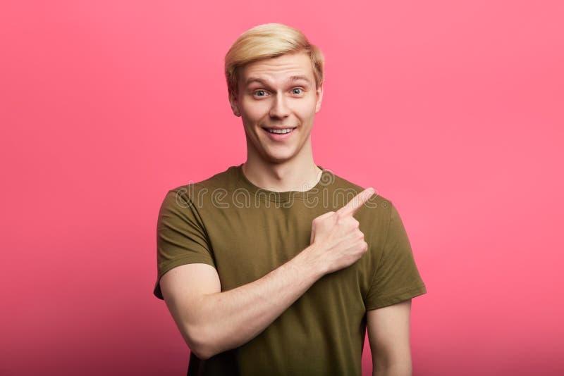 Vrolijke blonde modieuze kerel die de vinger ergens richten bij stock fotografie