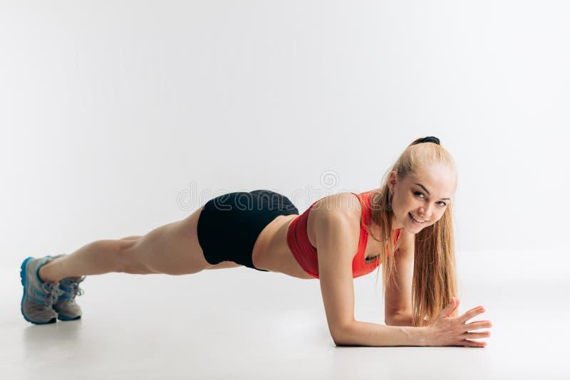 Vrolijke blondeatleet die plankoefeningen voor strakke, vlakke abs tonen royalty-vrije stock foto's