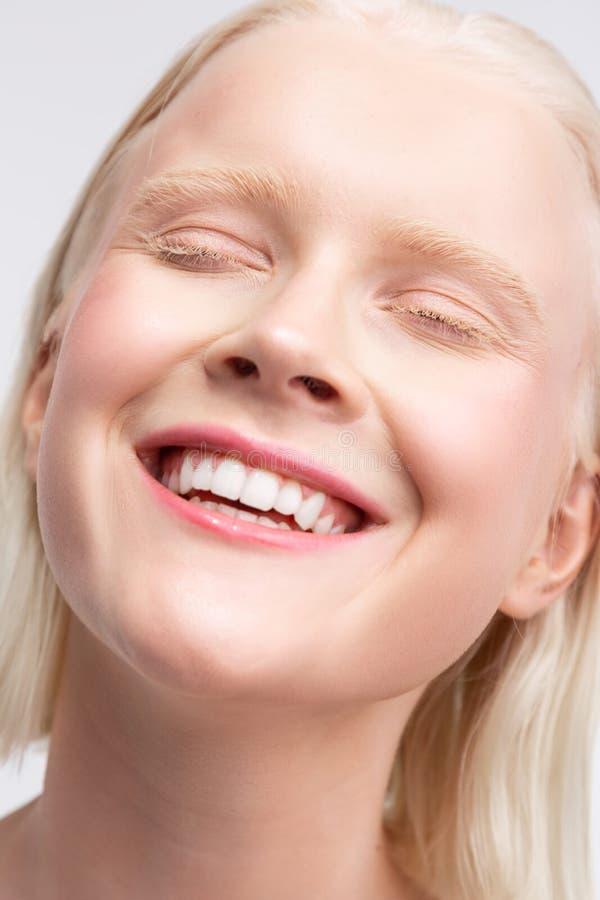 Vrolijke blondevrouw die met witte wenkbrauwen ruim glimlachen stock foto
