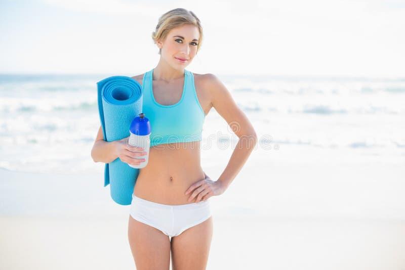 Vrolijke blondevrouw in sportkleding die een fles en een oefeningsmat dragen stock afbeelding