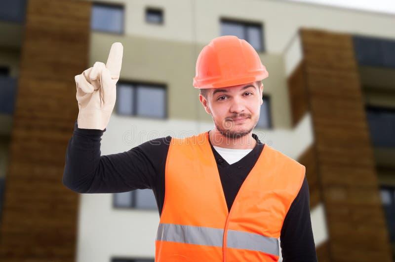 Vrolijke bouwer die zijn vinger benadrukken stock foto